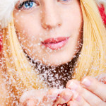 beautiful blonde woman blowing snow