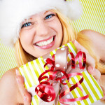 beautiful blonde woman holding a christmas gift is smiling